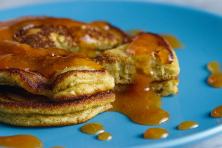 Homemade gluten free pancakes with peach jam served on sky blue plate. Close up shot