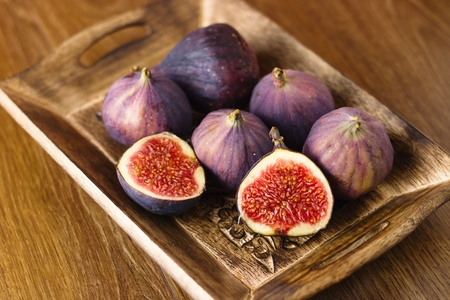 Beautiful ripe figs in rustic decorated wooden bowl