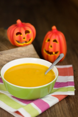 Simple plain pumpkin soup in green bowl. Homemade creamy soup of fall season with halloween decoration