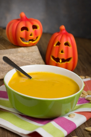 Creamy simple pumpkin soup in green dish. Decorated by halloween themed props and some pumpkin seeds Stock Photo - 88489623