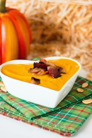 Heart shaped bowl of smooth creamy pumpkin soup with fried bacon