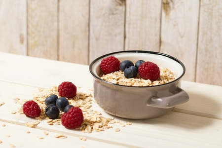 Rustic setting of healthy fiber-rich food oatmeal with blueberries and raspberries