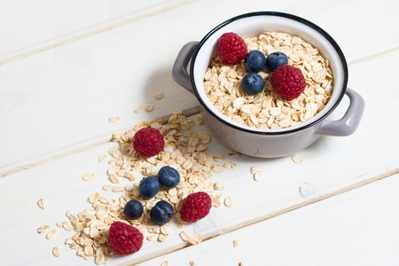 Rolled oatmeal in small pot decorated by fresh berries on white wooden board table,rustic setting,selective focus Stok Fotoğraf