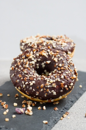 Several chocolate glazed donuts with chopped nuts Stock Photo