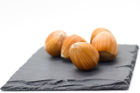 Several whole hazelnuts on small black slate board. Isolated on white