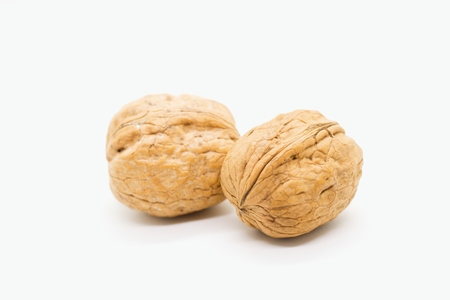 Two de-husked and dried walnuts isolated on white