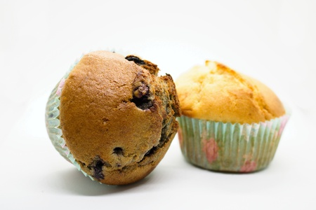 Vanilla muffin and blueberry muffin isolated on white. Blueberry cupcake knocked over.