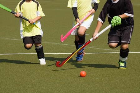 Children playing field hockey competitively. Two teammates in yellow jerseys chase running player in black uniform