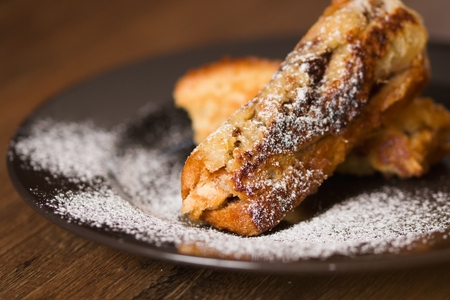 Detail on sugar coated rolled french toast on a plate.Shallow depth of field, selective focus