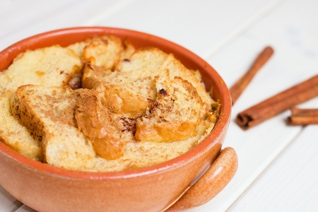 Bread pudding in earthenware pot and several cinnamon sticks on white wooden table