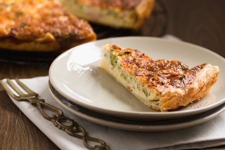 Triangle shaped piece of vegetable pie, or quiche, served on a plate with ornate brass fork
