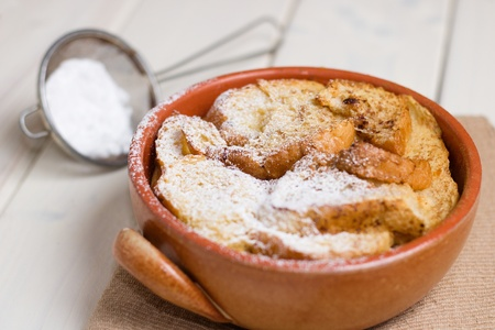 Bread pudding in earthenware pot and powdered sugar Stock Photo