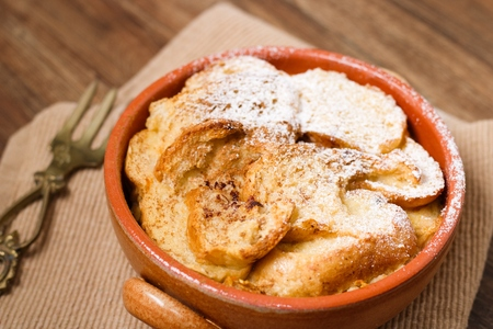 Earthenware pot of bread and butter pudding partially covered by powdered sugar