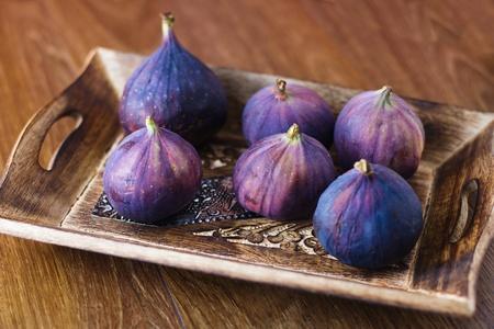 Ripe sweet  beautiful fruit - figs in rustic wooden bowl