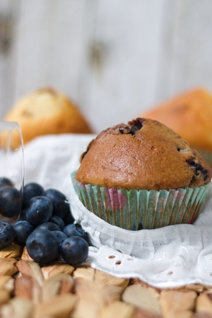 Blueberry muffin in rustic setting with white lace cloth