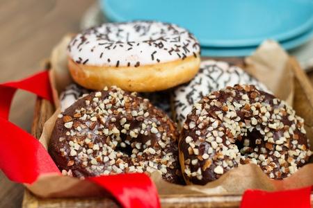 Several almonds sprinkled donuts in wooden box with red ribbon in front of blue plates stack Stockfoto