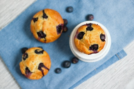Top down look on three homemade gluten free blueberry muffins. Selective focus on uffin set on white bowl Stockfoto