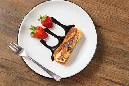 3Top down view on rolled french toast on a plate with strawberries and chocolate topping - decoratively served dessert