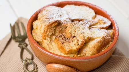 Powdered sugar coated bread pudding in earthenware pot and brass fork on white wooden board table