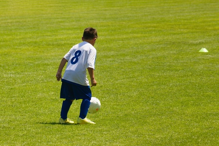Small kid practicing or playing soccer in blue and white uniform