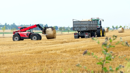 Heavy machinery collecting dried haystacks in the field