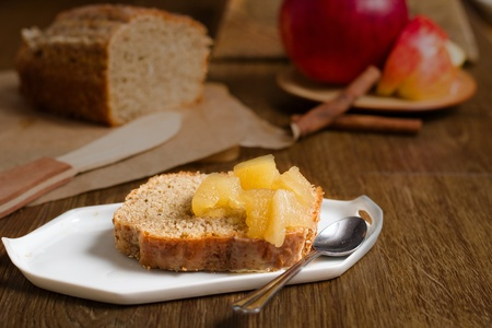Slice of cake baked from batter dough with apple sauce. Background contains whole loaf, apple and cinnamon sticks