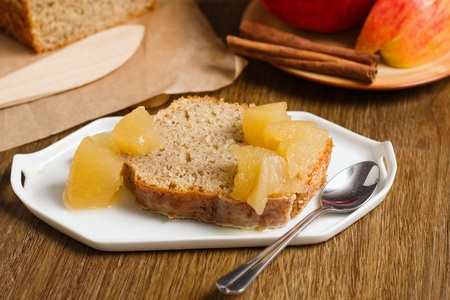 Piece of cake from batter mixture with juicy apple sauce. Served on small white plate on dark wood table
