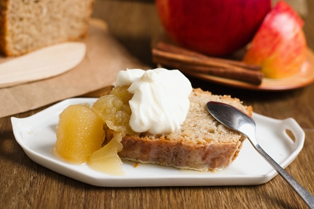 Batter cake served with juicy apple sauce and whipped cream on small white plate . Whole loaf, cinnamon sticks and apple in background