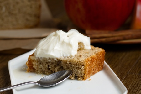 Slice of batter cake slice cut in half and served with juicy stewed apples and whipped cream custard on small white plate. Stockfoto