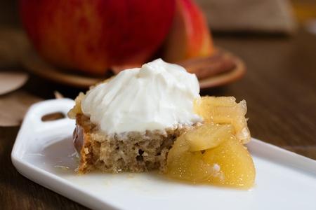 Cake slice cut in half, stewed apples and whipped cream custard on dark wood table