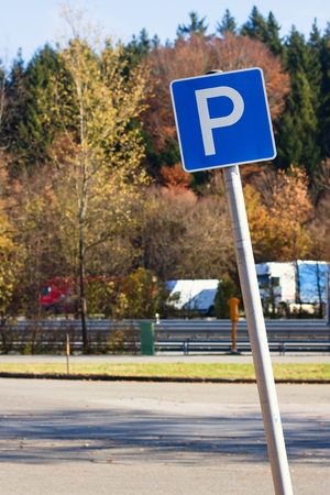 Parking sign at empty parking lot next to German highway (autobahn). Highway with trucks and van parking on other side in background