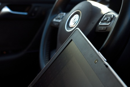 Laptop computer display in front of steering wheel of a car