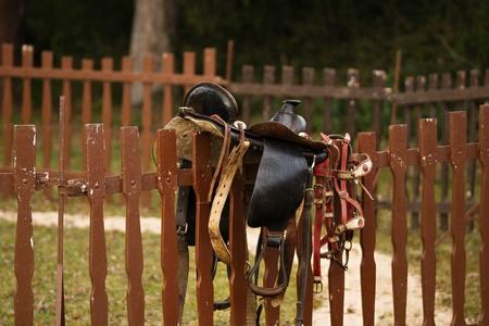 Empty western saddle on fence Stockfoto