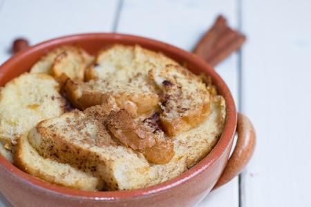 Earthenware pot of bread and butter pudding on white board table