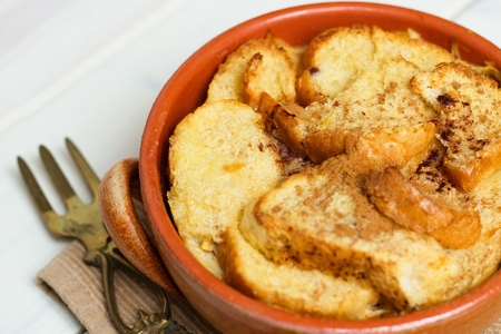 Close up on bread and butter pudding in brown earthenware pot on white wooden table