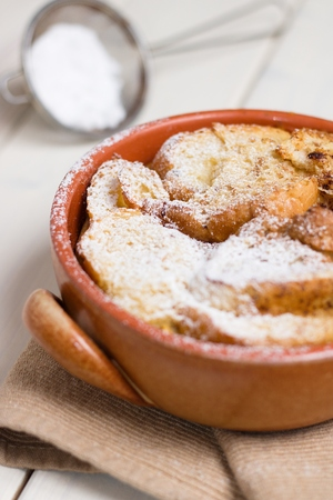 Bread pudding sprinkled with powdered sugar in earthenware pot Stockfoto