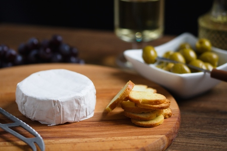 Small whole wheel of cheese with white rind (camembert or brie) on wooden board with roasted bread slices, olives and white wine Stockfoto