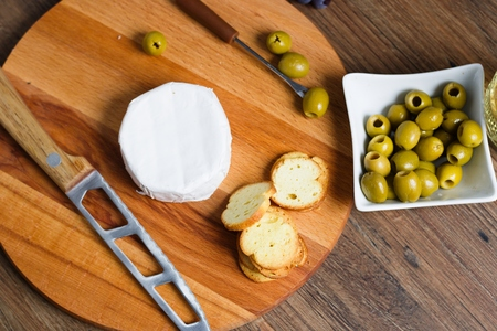 Wheel of camembert or brie with bread chips and green olives. Top down view
