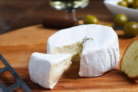 Close up shot of cut wheel of soft white rind cheese (camembert or brie) with small piece cut to show beautiful texture