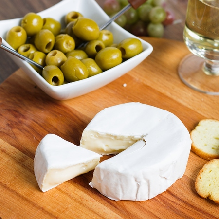 Soft cheese with white rind (camembert or brie). Cut triangle piece to show taxture of inside the cheese