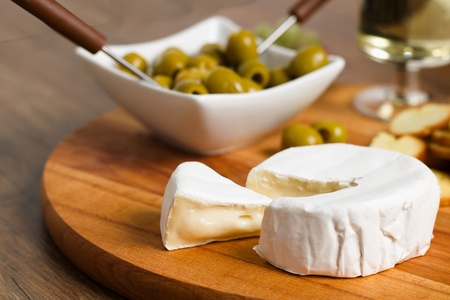 Camembert cheese on wooden board with roasted bread slices, olives and white wine
