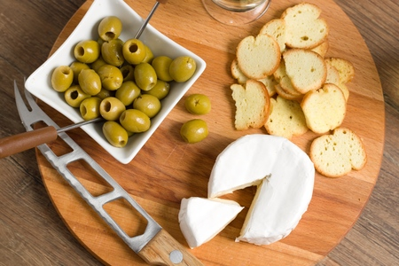 Top down view of soft cheese (camembert or brie) on wooden board with roasted bread slices and olives, Connoiseur party food, concept of quality luxury eating