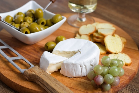 Triangle shaped piece of camembert cheese cut out from whole wheel and served with bread chips,olives,grapes and wine