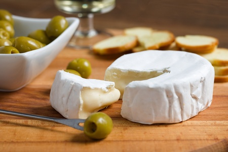Soft cheese with white rind (camembert or brie) on wooden board with roasted bread slices, olives and white wine