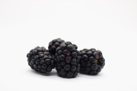 Several ripe blackberries isolated on white background