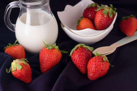 Red ripe fresh strawberries on dark blue background with white bowls and jug of milk or cream