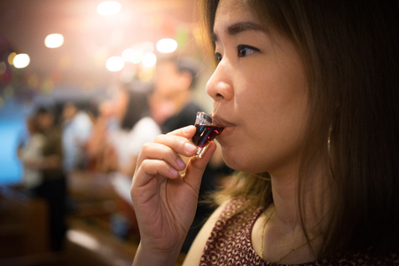 A believer is drinking a cup of red wine in a Holy Communion. Stock Photo