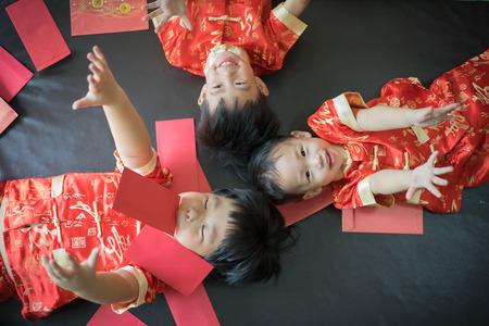 Frohes chinesisches neues Jahr . 3 nette asiatische kleine Spielwaren spielen rote Umschläge zusammen auf dem Bett Standard-Bild - 93551036