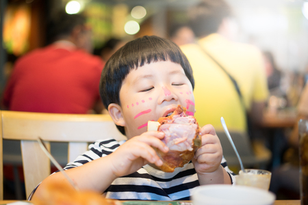 A painted face boy is eating delicious pork knuckle in a steak restaurant.