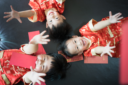 Happy chinese new year. 3 cute asian little boys are playing red envelopes together on the bed. There are Chinese blessing words Longevity, auspicious and wealthy in the Chinese suit.